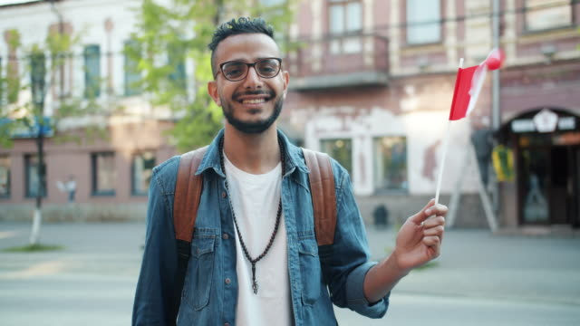 portrait of attractive abarian guy holding canadian flag in the street smiling - canada flag stock videos & royalty-free footage