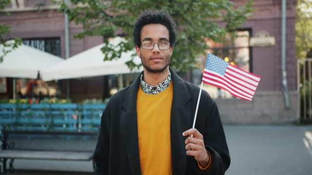 Video Portrait of attractive African American student standing outdoor holding US flag