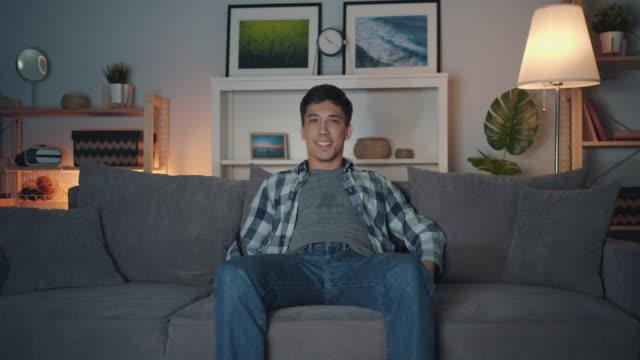 vídeos de stock, filmes e b-roll de retrato do indivíduo asiático atrativo que presta atenção à tevê que tem o divertimento rir no quarto escuro - solteiros jovens