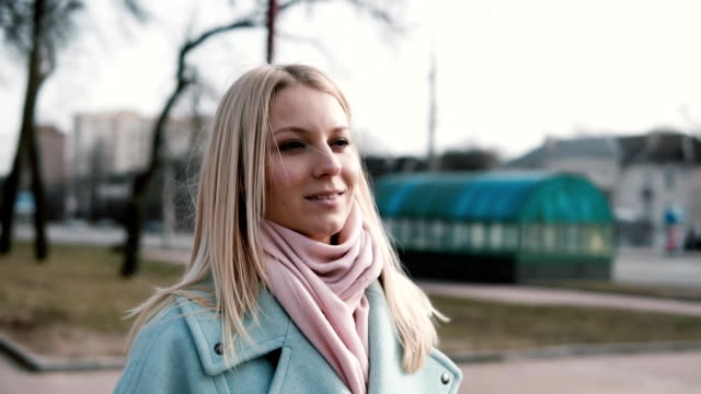 Portrait of attractive Caucasian blonde woman. Anticipation and excitement. Adult 30s female in stylish coat and scarf video