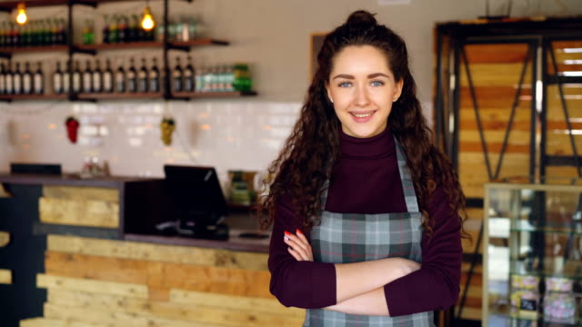 portrait of attractive confident woman small business owner standing in her opening coffee shop and smiling looking at camera. coffee house interior in background. - длина стоковые видео и кадры b-roll