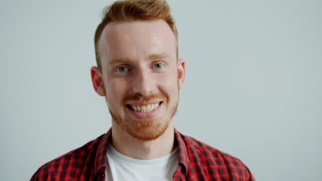 porträtt av attraktiv kille i casual kläder leende skrattar på grå bakgrund - rött hår bildbanksvideor och videomaterial från bakom kulisserna