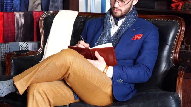 暗いコートとトレンディなスーツの屋内仕立て屋で魅力的な男性の肖像画 - スタイリッシュ点の映像素材/bロール