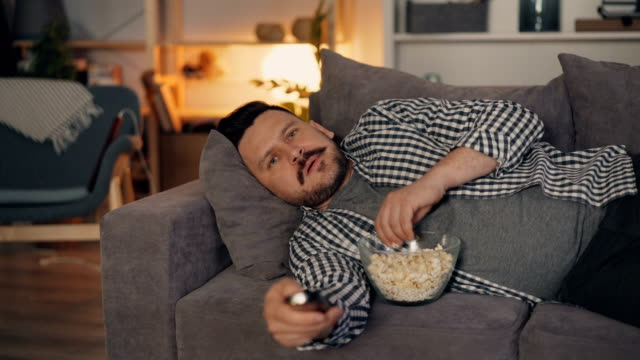Portrait of attractive man watching film on TV at night at home cozy apartment