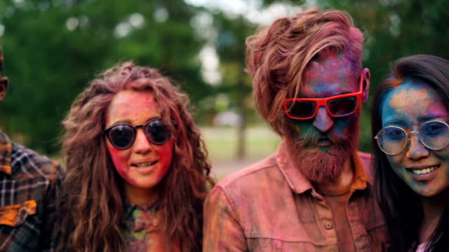 vídeos de stock e filmes b-roll de portrait of attractive people multiracial group with colorful faces, hair and clothing standing outdoors, looking at camera and smiling. holi festival, party and fun concept. - holi