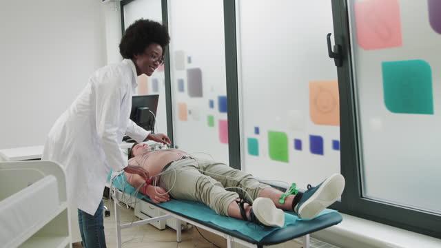 porträtt av attraktiv positiv afroamerikansk kvinnlig läkare tittar på kameran. yrke, sjukhus, sjukvård. läkare kardiolog ansluter patienten till ekg-maskinen. förberedelser för kardiogram - tema bildbanksvideor och videomaterial från bakom kulisserna