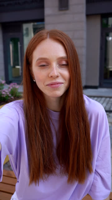 portrait of attractive redhead girl welcoming person on phone during online video communication. - вертикальный стоковые видео и кадры b-roll