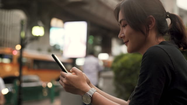 Portrait of attractive smiling typing on the screen of the smartphone while chatting