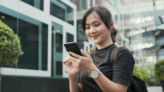 Portrait of attractive smiling typing on the screen of the smartphone while chatting video
