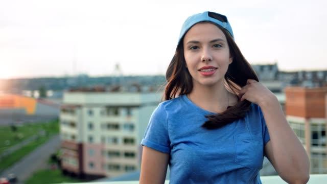 vídeos de stock, filmes e b-roll de retrato de mulher bonita e sorridente jovem adolescente em cap tocar seu cabelo ao ar livre - característica arquitetônica