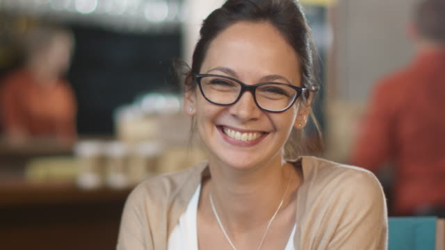 portrait of attractive smiling young woman at cozy coffee shop. - denti video stock e b–roll