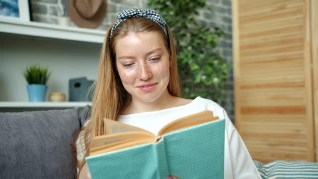 stockvideo's en b-roll-footage met portret van aantrekkelijke tiener meisje lezen boek thuis glimlachen draaien van pagina's - literatuur
