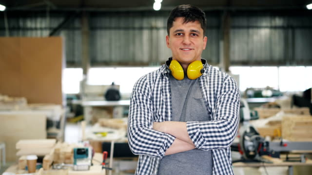 Portrait of attractive young joiner standing in workshop with arms crossed Portrait of attractive young joiner standing in workshop with arms crossed smiling and looking at camera. Profession, people and small business concept. carpenter stock videos & royalty-free footage