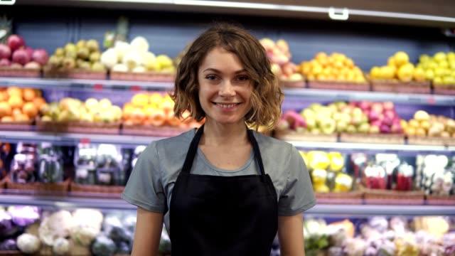 Porträt einer attraktiven jungen Verkäuferin in schwarzer Schürze, die im Supermarkt mit Regalen mit Früchten im Hintergrund steht, in die Kamera schaut und lächelt. Handels- und Personenkonzept – Video