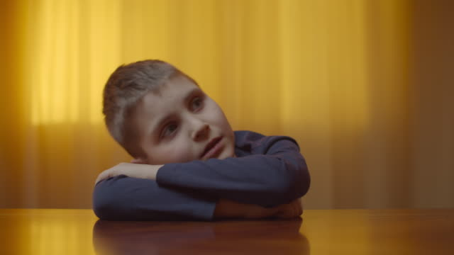 Portrait of autistic boy showing emotions sitting at the desk. Kid with autism closing eyes because of bright light at home. Autism awareness Portrait of autistic boy showing emotions sitting at the desk. Kid with autism closes eyes because of bright light at home. Autism awareness autism stock videos & royalty-free footage