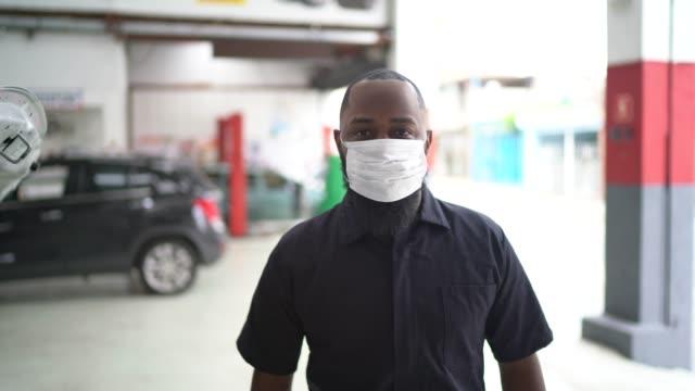 vídeos de stock e filmes b-roll de portrait of auto mechanic man at auto repair shop - afro latino mask