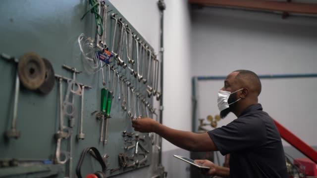 vídeos de stock, filmes e b-roll de retrato de mecânico de automóveis em oficina de reparação de automóveis - pequenas empresas