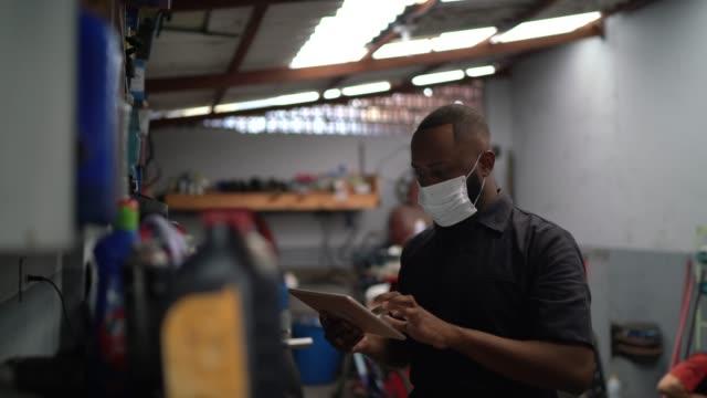 Portrait of auto mechanic man using digital tablet at auto repair shop Portrait of auto mechanic man at auto repair shop african ethnicity stock videos & royalty-free footage