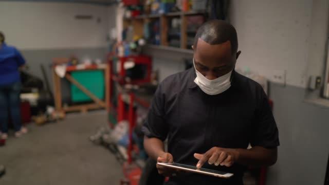 portrait of auto mechanic man using digital tablet at auto repair shop - warsztat filmów i materiałów b-roll
