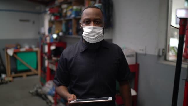 vídeos de stock e filmes b-roll de portrait of auto mechanic man using digital tablet at auto repair shop - afro latino mask