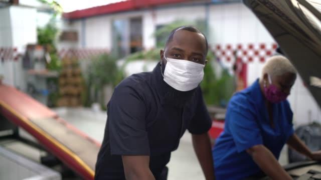 vídeos de stock e filmes b-roll de portrait of auto mechanic partners at auto repair shop - afro latino mask