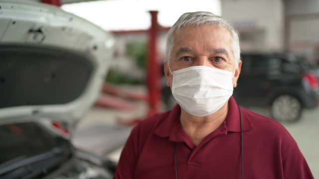 vídeos de stock e filmes b-roll de portrait of auto mechanic senior man at auto repair shop - mecânico