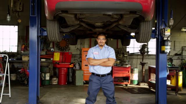 Portrait of auto mechanic standing in shop video