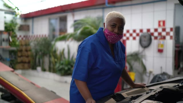 vídeos de stock e filmes b-roll de portrait of auto mechanic woman at auto repair shop - afro latino mask