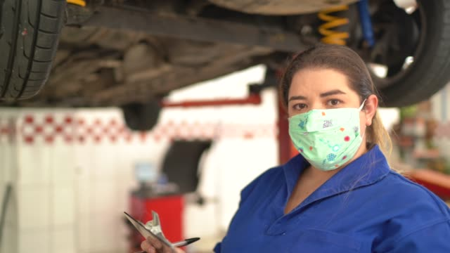 portrait of auto mechanic woman doing checklist at auto repair shop - essential workers stock videos & royalty-free footage