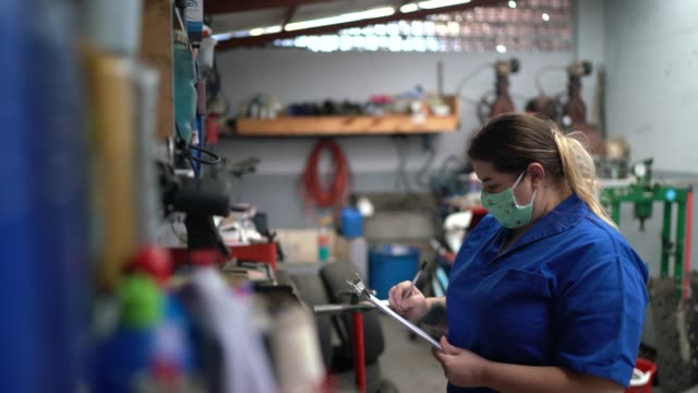 Portrait of auto mechanic woman doing checklist at auto repair shop video