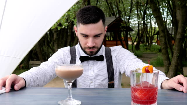 Portrait of barman at work, barkeeper close-up, bartender behind bar, barmen submit alcohol, colored chilled drinks on bar counter video