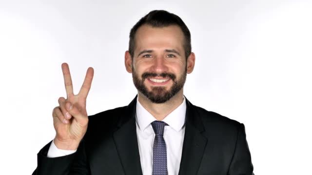 portrait of beard businessman gesturing  victory sign - campionato video stock e b–roll