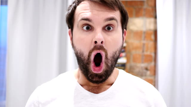 portrait of beard man gesturing shock, astonished, indoor - sorpresa video stock e b–roll