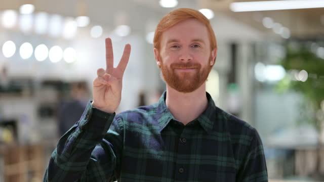vídeos y material grabado en eventos de stock de retrato de beard redhead man with victory sign by hand - brazo humano