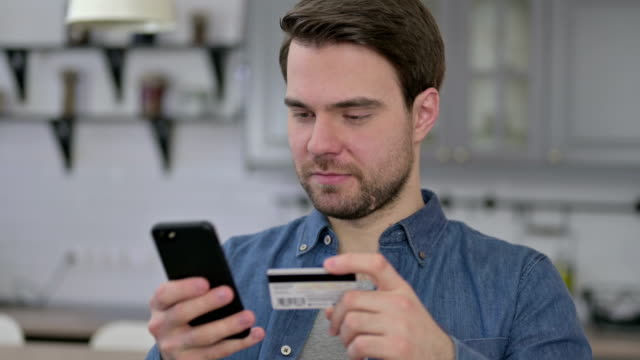 Portrait of Beard Young Man using Credit Card on Smartphone