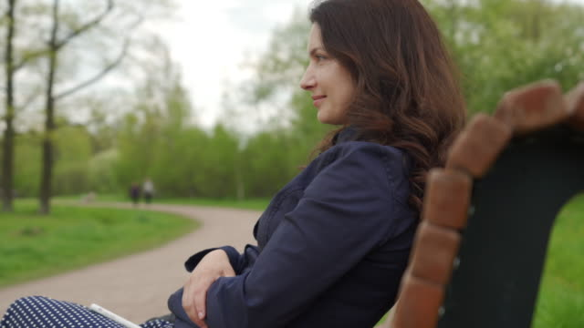 portrait of beautiful adult brunette woman with long hair on bench in a park - садовая скамья стоковые видео и кадры b-roll