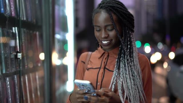 porträt der schönen afro frau mit handy - brasilianischer abstammung stock-videos und b-roll-filmmaterial