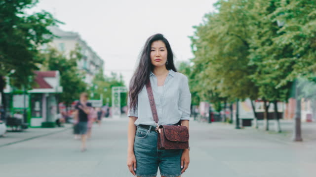 Portrait of beautiful Asian student stanidng in city street with serious face Portrait of beautiful Asian girl student stanidng in busy city street with serious face looking at camere while people men and women are walking around. student life stock videos & royalty-free footage