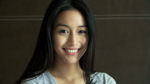 4K: Portrait of beautiful Asian woman in bed smiling to the camera video