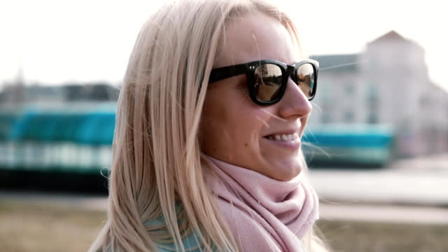Portrait of beautiful blonde hair Caucasian woman. Happy smiling pretty young 20s girl in stylish sunglasses side view video