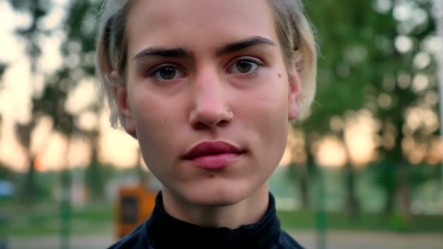 Portrait of beautiful blonde woman with pierced nose looking at camera and smiling, nodding in agreement, park in background