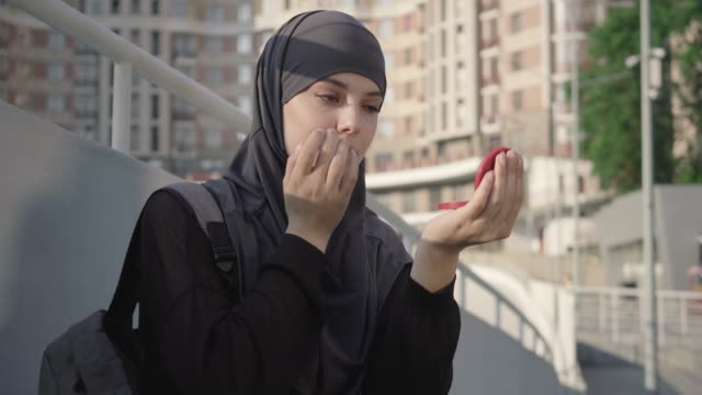 Portrait of beautiful brown-eyed muslim woman correcting makeup outdoors. Charming young Middle Eastern girl in hijab applying face powder with finger. Beauty, skin care, lifestyle, femininity.