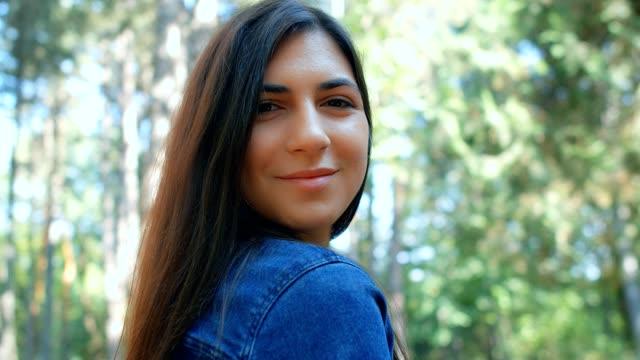 porträtt av vacker brunett flicka flirta med kameran i parken, 4k slow motion - människorygg bildbanksvideor och videomaterial från bakom kulisserna