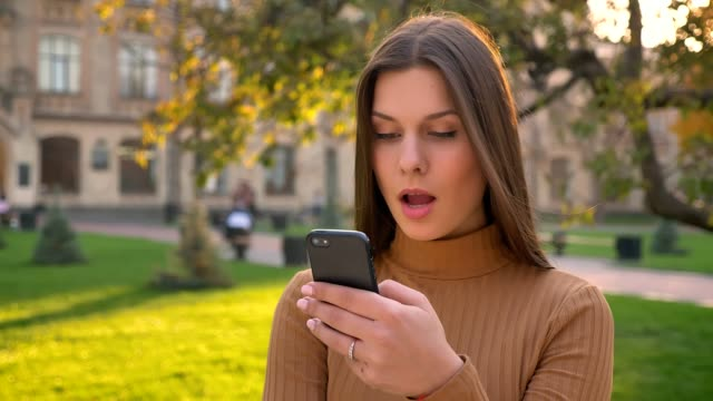 Portrait of beautiful brunette girl scrolling the feed using smartphone with various emotions on green park background. Portrait of beautiful brunette girl scrolling the feed using smartphone with various emotions on green park background sideways glance stock videos & royalty-free footage