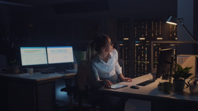 porträt der schönen geschäftsfrau verwendet desktop computer, typisierung auf einem keyboard, monitoring business transactions, signing contracts. arbeitet ende bei nacht im big corporate office - verantwortung stock-videos und b-roll-filmmaterial
