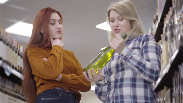 Portrait of beautiful Caucasian girls thinking on the choice of wine in supermarket. Blond and redhead women talking as standing in liquor store. Alcohol industry, leisure, lifestyle, shopping.