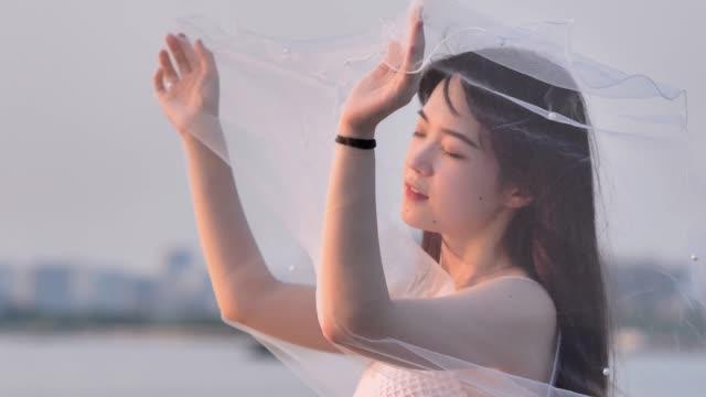 白い花嫁のドレスで美しい中国の女の子の肖像画は、目を閉じて、風の強い夕暮れで手にベールを持って、ぼかし川の水の背景、美しさ、ロマンチックなコンセプト、4k映像、スローモーシ� - 美人点の映像素材/bロール