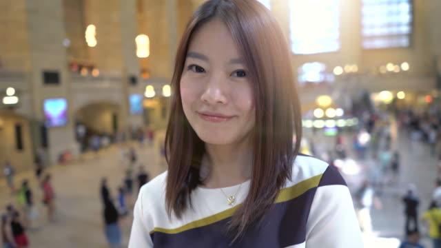 外の楽しい日を過ごして美しい中国の女性の肖像画。笑顔と元気な街を観光します。 - 米国旅行点の映像素材/bロール