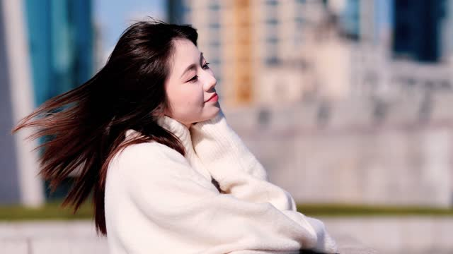 vídeos de stock e filmes b-roll de portrait of beautiful chinese young woman enjoy sunshine and breeze with shanghai city building background in sunny day, shiny black long hair flying in wind, 4k slow motion footage. - cabelo preto