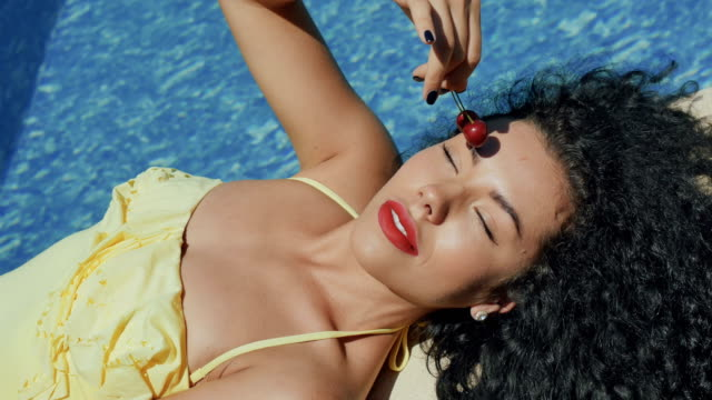 Portrait of beautiful curly brunette sexy eats cherries Beautiful sensual girl with red lips lays near the swimming pool and poses for camera. Gorgeous model with curly hair enjoys a hot weather and eats a cherry. Pretty woman touches a berries on her face. cherry stock videos & royalty-free footage